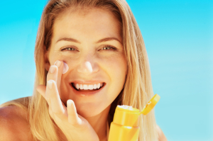 smiling young woman applying suncreen