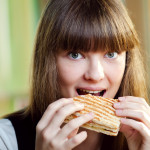 Portrait of young woman with sandwich