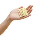 woman hand holding contraceptive pills