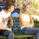 Young couple sitting at opposite ends of a bench.