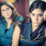 Teenager problems - Defiant teenage girl after a fight with her worried mother looking at her
